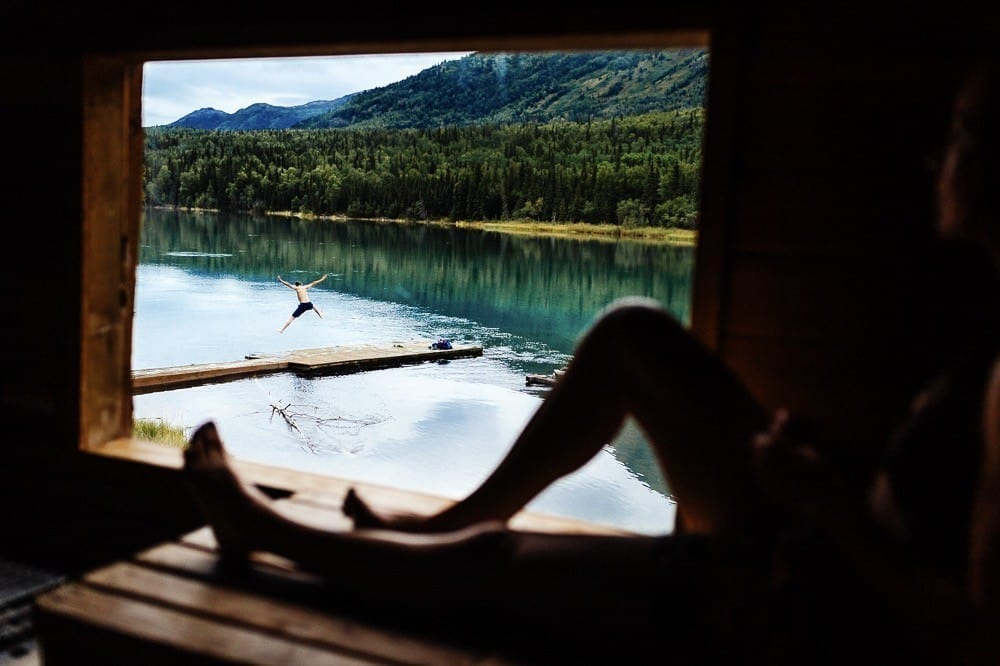 Person sitting in sauna looking out window of mountain river